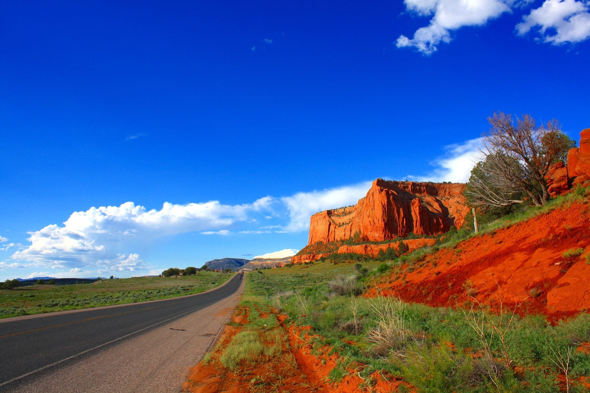 scenic picture taken next to road displaying red mountains of arizona