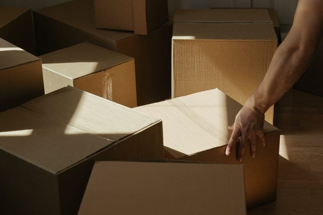 Person'S Arm Grabbing A Box  Amongst A Pile Of Boxes For Blog Post How To Move Out Of Your Parents House