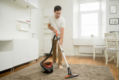 Happy Smiling Man Cleaning The Carpet