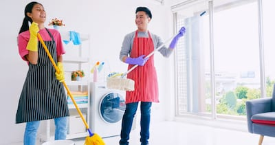 Husband And Wife Having Fun While Cleaning Their Room. Happy Asian Couple Spending Time Together At Home.