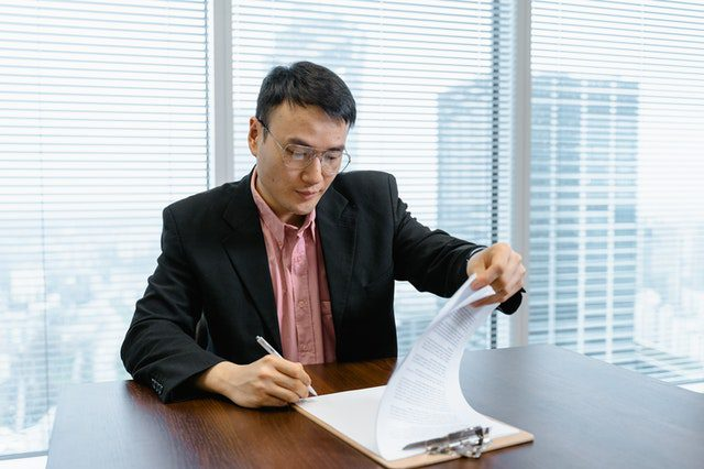 Businessman Flipping Through Pages On A Notebook In An Office For Article How Much Property Mangers Earn