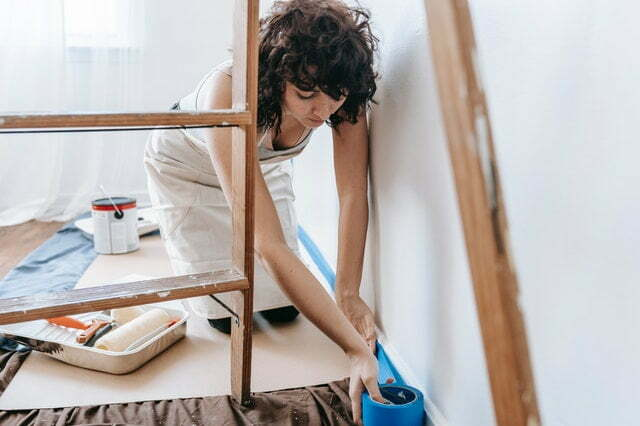 a woman adding a strip of painter's tape to the baseboard